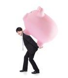Lycklig affärsman som bär den rosa spargrisen Fotografering för Bildbyråer