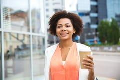 Lycklig afrikansk affärskvinna med kaffe i stad royaltyfri bild