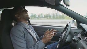 Lycklig afrikansk amerikanaffärsman som surfar socialt massmedia på hans minnestavladatorsammanträde inom hans bil