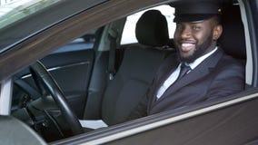 Lycklig afrikansk amerikanchaufför som ser in i kameran, lyxig överföring, service arkivfoto