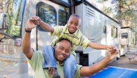 Lycklig afrikansk amerikanfader och son framme av deras RV royaltyfri bild