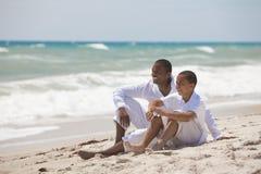 Lycklig afrikansk amerikanfader och Son på strand Arkivfoton