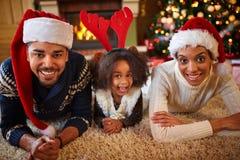 Lycklig afrikansk amerikanfamilj med jultomtenhattar fotografering för bildbyråer