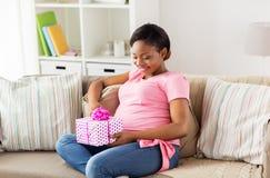 Lycklig afrikansk amerikangravid kvinna med gåvan arkivfoto