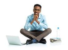 Lycklig afrikansk amerikanhögskolestudent med bärbara datorn, böcker och bo Arkivbild