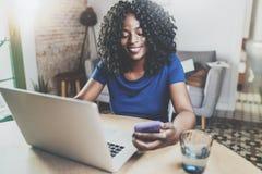 Lycklig afrikansk amerikankvinna som använder bärbara datorn och smartphonen, medan sitta på trätabellen i vardagsrummet horisont royaltyfri bild