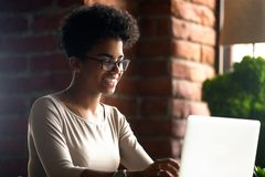 Lycklig afrikansk amerikankvinna som använder bärbara datorn som pratar med vänner royaltyfri bild
