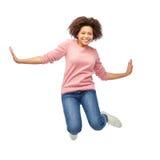 Lycklig afrikansk amerikankvinna som hoppar över vit royaltyfri bild