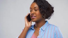 Lycklig afrikansk amerikankvinna som kallar på smartphonen stock video