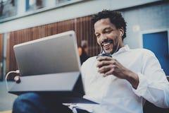 Lycklig afrikansk amerikanman i hörlurar som gör den videopd appellen via det elektroniska handlagblocket pro- med bort kaffe för Arkivbild
