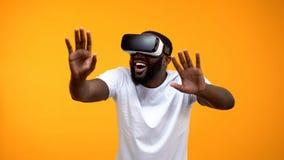 Lycklig afrikansk amerikanman som anv?nder unders?kande framtida teknologier f?r VR-h?rlurar med mikrofon arkivfoto