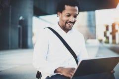 Lycklig afrikansk amerikanman som arbetar med det elektroniska handlagblocket som är pro- med innehavet i händer Begrepp av grabb Arkivbild