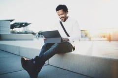 Lycklig afrikansk amerikanman som arbetar med det elektroniska handlagblocket som är pro- med innehavet i händer Begrepp av grabb Royaltyfri Fotografi