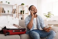 Lycklig afrikansk amerikanman som förbereder sig för att resa som talar på telefonen arkivbilder