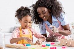 lycklig afrikansk amerikanmoder och dotter som tillsammans gör kakor med kakaskärare arkivbilder