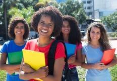 Lycklig afrikansk amerikanstudent med den lilla gruppen av latin- och caucasianflickor arkivbilder