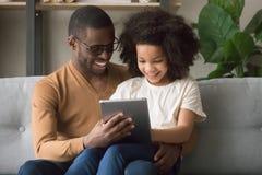 Lycklig afrikansk fader- och ungedotter som använder den digitala minnestavlan arkivfoton