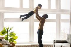 Lycklig afrikansk fader som lyfter upp i liten son för luft royaltyfri foto