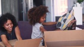 Lycklig afrikansk familj som har roliga packande upp askar på rörande dag stock video