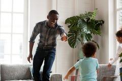 Lycklig afrikansk farsa som skrattar spring i vardagsrum som fångar ungar royaltyfria foton