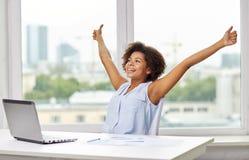 Lycklig afrikansk kvinna med bärbara datorn på kontoret arkivfoton