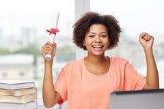 Lycklig afrikansk kvinna med bärbara datorn, böcker och diplomet Fotografering för Bildbyråer