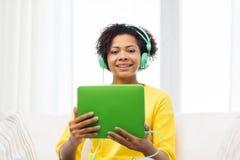 Lycklig afrikansk kvinna med minnestavlaPC och hörlurar Royaltyfri Bild