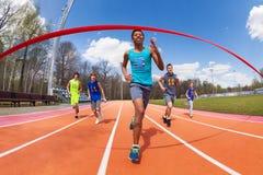 Lycklig afrikansk sprinter som kör till mållinjen arkivfoton