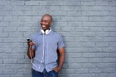 Lycklig afrikansk ung man med hörlurar och mobiltelefonen Royaltyfri Foto