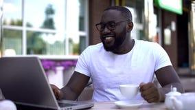 Lycklig afro--amerikan man som smsar med släktingar på bärbara datorn som sitter i restaurang royaltyfria foton