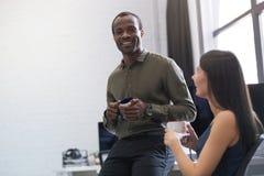 Lycklig afro amerikansk grabb som pratar med en kvinnlig kollega royaltyfri bild