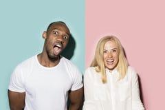 Lycklig afro man och kvinna Dynamisk bild av den caucasian kvinnlign och afro manlig modell på rosa studio royaltyfri foto