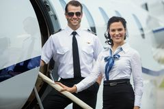 Lycklig Airhostess och pilot Standing On Private Royaltyfri Foto
