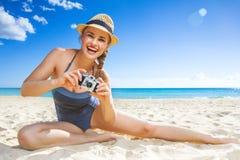 Lycklig aktiv kvinna på seacoasten som tar fotoet med den digitala kameran Royaltyfri Fotografi