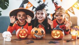 Lycklig allhelgonaafton! en grupp av barn i dräkter och med pumpor arkivbild