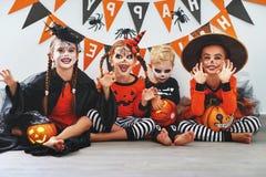 Lycklig allhelgonaafton! en grupp av barn i dräkter och med pumpor royaltyfri foto