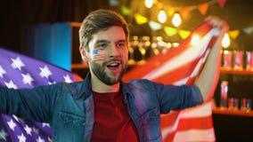 Lycklig amerikansk vinkande nationsflagga för fotbollfan som hurrar för favorit- lag arkivfilmer