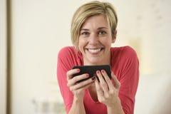 Lycklig användande internet app för ung härlig Caucasian kvinna på att le för mobiltelefon som är lyckligt arkivfoto