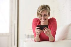 Lycklig användande internet app för ung härlig Caucasian kvinna på att le för mobiltelefon som är lyckligt fotografering för bildbyråer