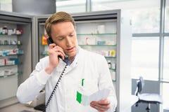 Lycklig apotekare på telefonen Arkivbild