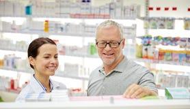 Lycklig apotekare som talar till den höga mannen på apotek arkivbilder