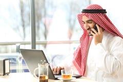 Lycklig arabisk man som använder en bärbar dator och talar på telefonen i en stång arkivbilder