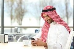 Lycklig arabisk man som använder en smart telefon i en coffee shop arkivbild
