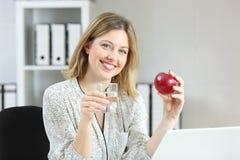 Lycklig arbetare som poserar rymma ett äpple på kontoret Arkivbilder