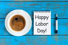 Lycklig arbets- dag - meddelande i notepad på den blåa lantliga tabellen med morgonkaffekoppen Labour dag som firas på Maj 1 Royaltyfria Bilder