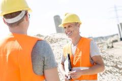 Lycklig arbetsledare som diskuterar med kollegan på konstruktionsplatsen Fotografering för Bildbyråer