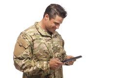 Lycklig armésoldat som läser den digitala minnestavlan fotografering för bildbyråer