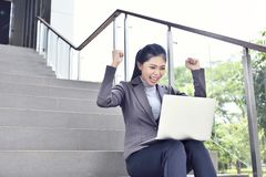 Lycklig asiatisk affärskvinna med bärbar datorarbete arkivbilder