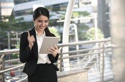 Lycklig asiatisk affärskvinna som använder den digitala minnestavladatoren royaltyfria foton