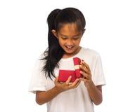 Lycklig asiatisk barnflicka med den röda gåvaasken royaltyfri fotografi